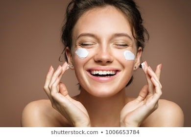 smiling lady applying face cream